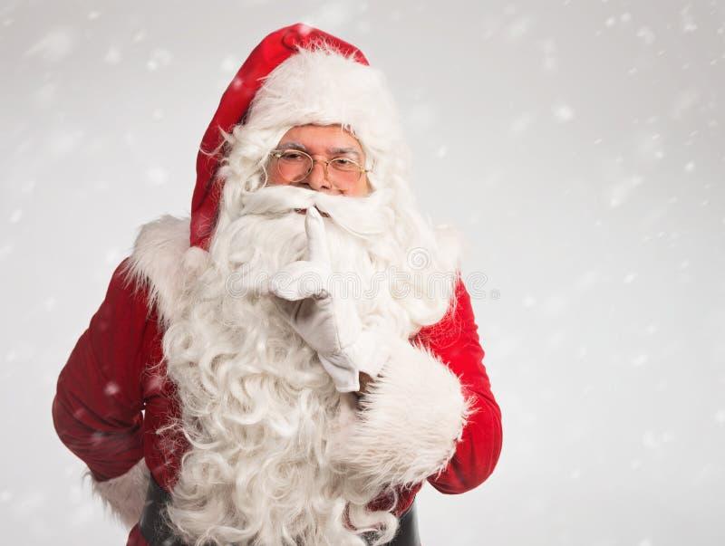Santa Claus que faz um gesto do silêncio, no fundo nevado fotos de stock