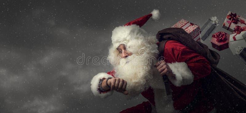 Santa Claus que funciona con y que entrega los regalos imágenes de archivo libres de regalías