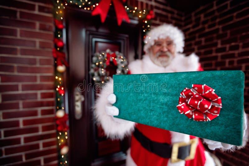 Santa Claus que guarda a caixa de presente, mãos gloved de Santa Claus que guardam g imagens de stock royalty free