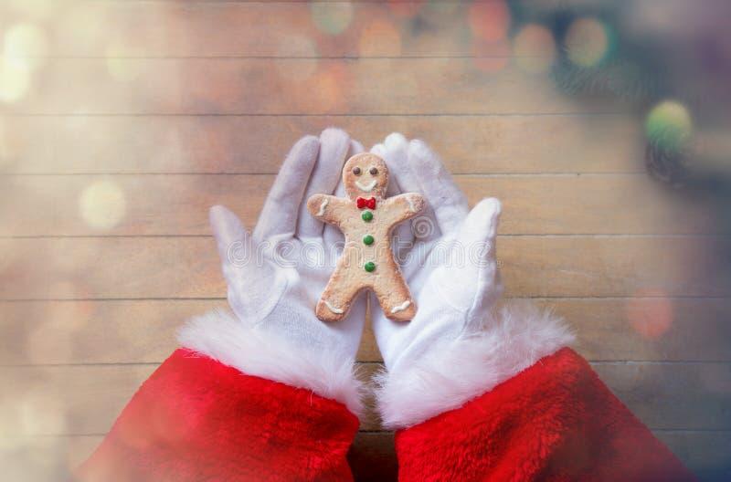 Santa Claus que guarda a cookie de Chrstmas imagem de stock