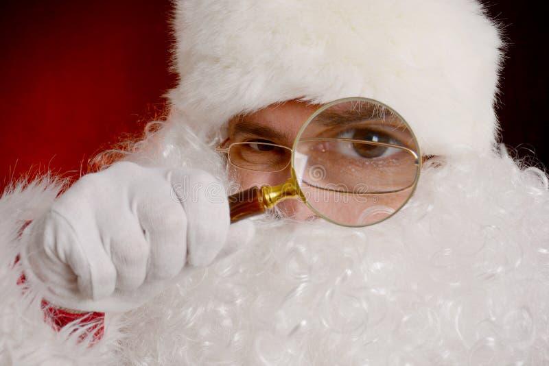 Santa Claus que guarda a lupa imagens de stock royalty free