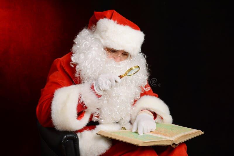 Santa Claus que guarda a lupa e que olha o mapa imagem de stock