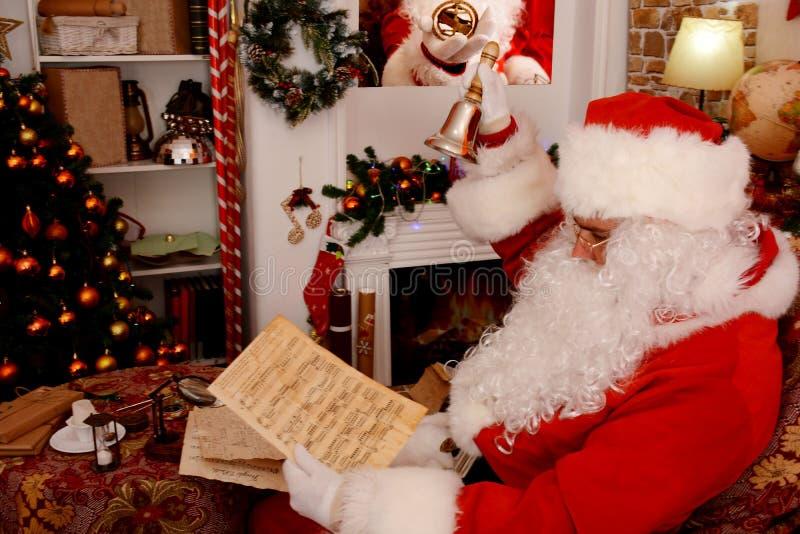 Santa Claus que guarda o sino de mão e o manuscrito musical, folha de música imagem de stock