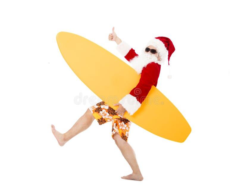 Santa Claus que guarda a placa de ressaca com polegar acima fotografia de stock