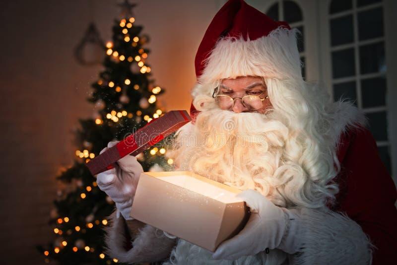 Santa Claus que guarda um presente, árvore de Natal no fundo imagens de stock royalty free