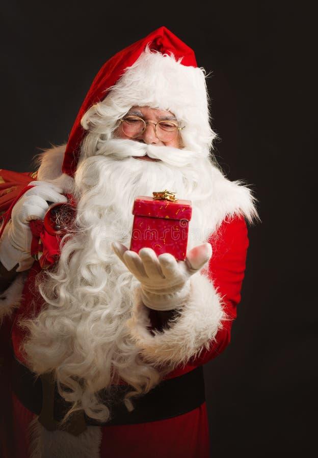 Santa Claus que guarda um presente, sobre um fundo escuro fotografia de stock