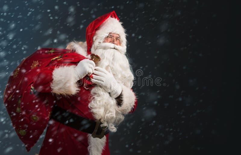 Santa Claus que guarda um saco com presentes e que soa um sino em um fundo escuro imagens de stock