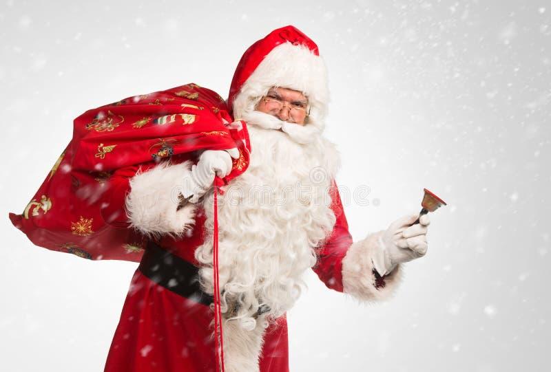 Santa Claus que guarda um saco com presentes e que soa um sino sobre fundo branco/cinzento foto de stock