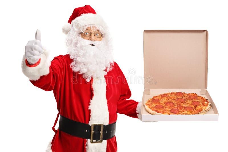 Santa Claus que guarda uma caixa da pizza e que faz um polegar acima do sinal imagens de stock royalty free