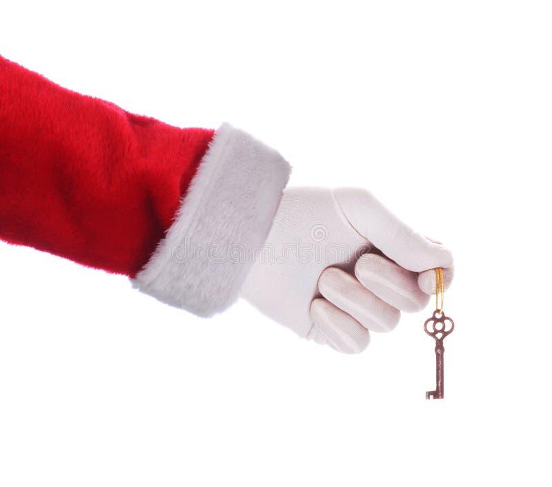Santa Claus que guarda uma chave sobre um fundo branco fotos de stock