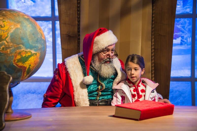 Santa Claus que guarda uma menina em seus braços na frente de seu de fotografia de stock royalty free
