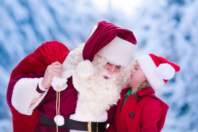 Santa Claus que habla con la niña en parque nevoso imagen de archivo