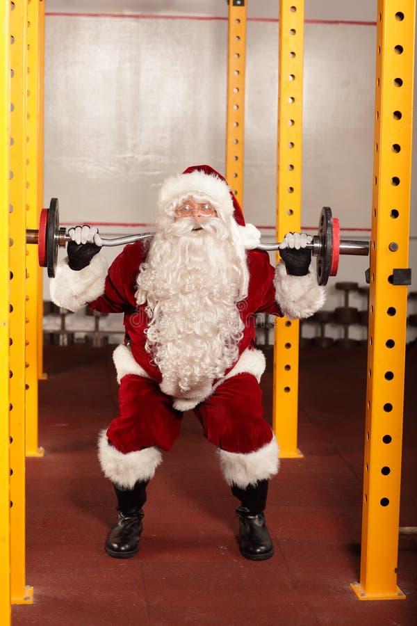 Santa Claus que levanta peso no gym imagens de stock royalty free