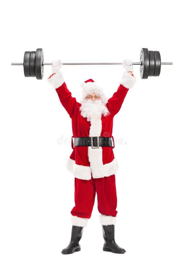 Santa Claus que levanta un barbell pesado foto de archivo