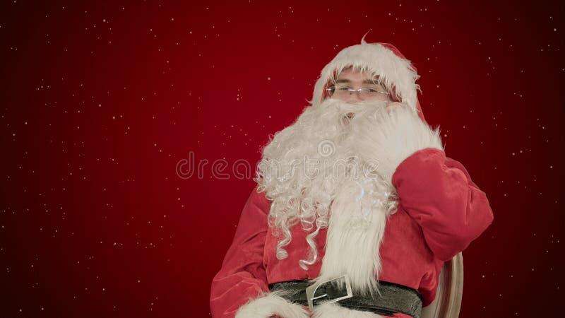 Santa Claus que llama con un teléfono móvil en fondo rojo con nieve imagen de archivo