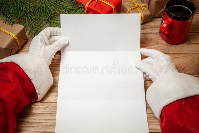 Santa Claus que lleva a cabo la letra en la tabla de madera con las cajas de regalo y árbol de navidad y taza de café o de té cal fotografía de archivo libre de regalías