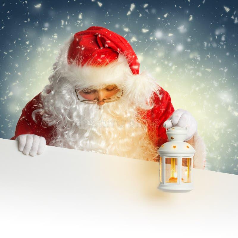 Santa Claus que mira abajo en la tenencia en blanco blanca de la bandera imágenes de archivo libres de regalías
