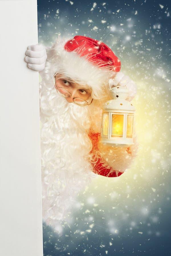 Santa Claus que mira de detrás bandera en blanco blanca imagen de archivo libre de regalías