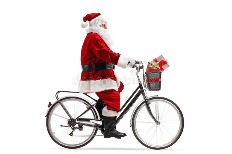 Santa Claus que monta uma bicicleta fotografia de stock
