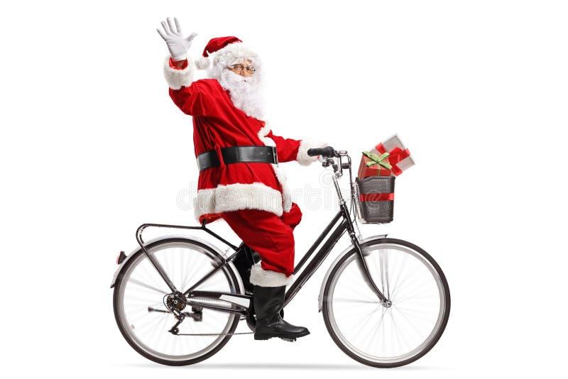 Santa Claus que monta uma bicicleta e uma ondulação fotografia de stock
