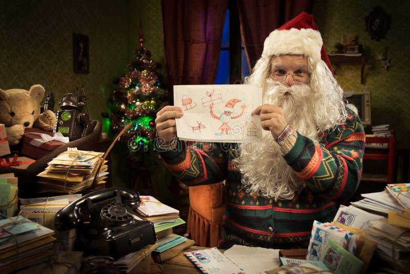 Santa Claus que mostra um desenho da criança fotografia de stock royalty free