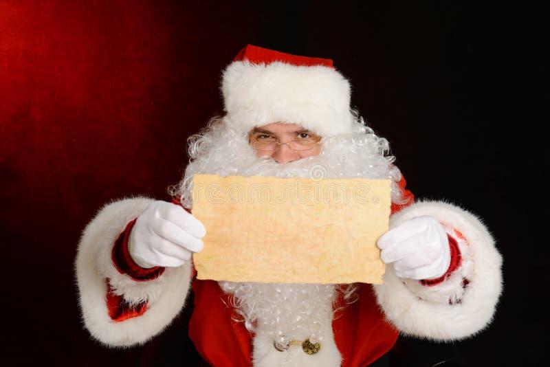 Santa Claus que mostra uma letra foto de stock