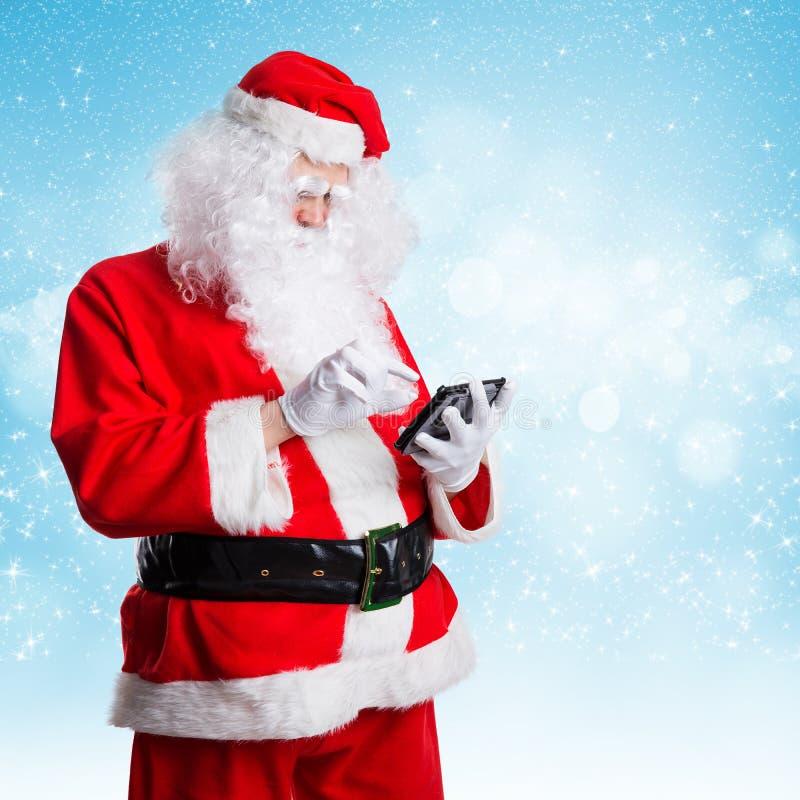 Santa Claus que olha algo acima em sua tabuleta foto de stock