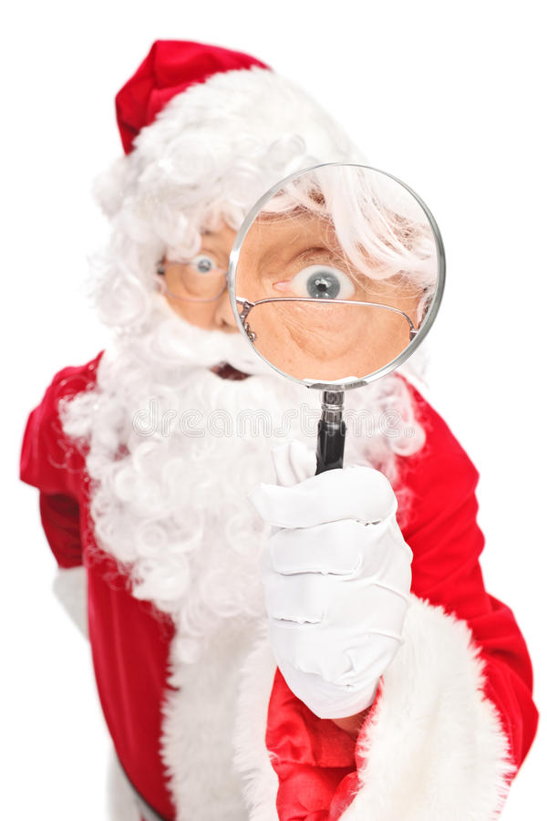 Santa Claus que olha através da lupa imagens de stock royalty free