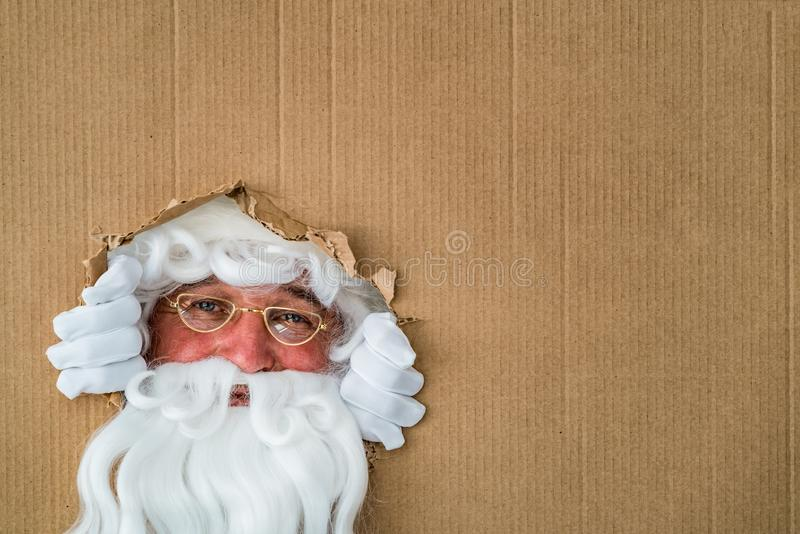Santa Claus que olha através do furo no cartão imagem de stock