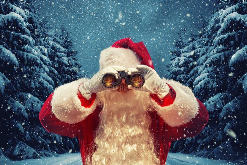 Santa Claus que olha através dos binóculos Conceito do Natal foto de stock