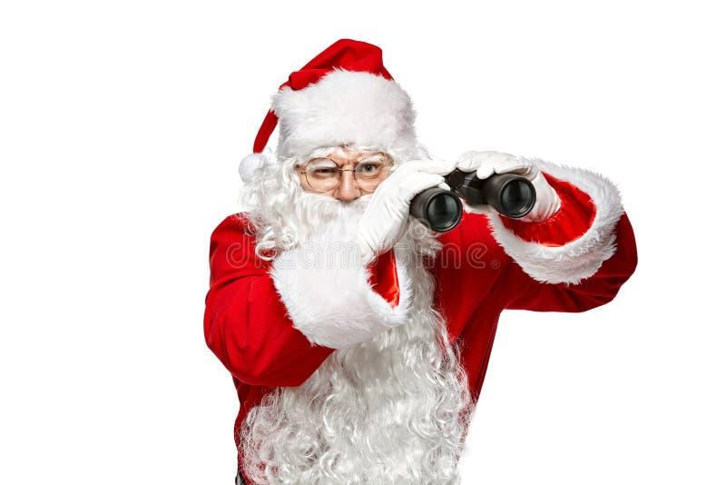 Santa Claus que olha através dos binóculos Isolado no fundo branco imagem de stock royalty free