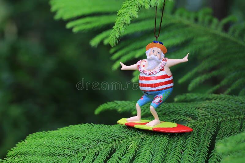 Santa Claus que practica surf en árbol de pino del cocinero foto de archivo