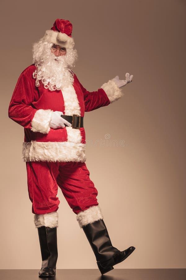 Santa Claus que presenta algo en su izquierda foto de archivo libre de regalías