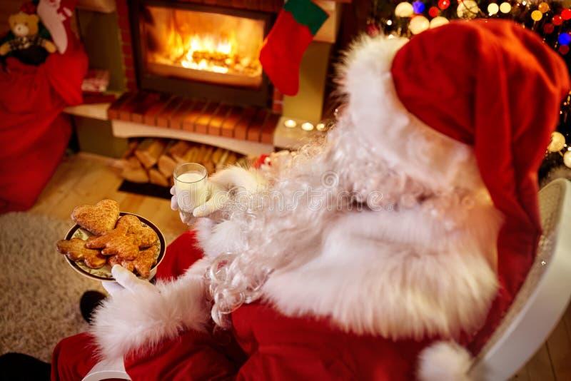 Santa Claus que relaxa em casa com leite e as cookies frescas imagens de stock