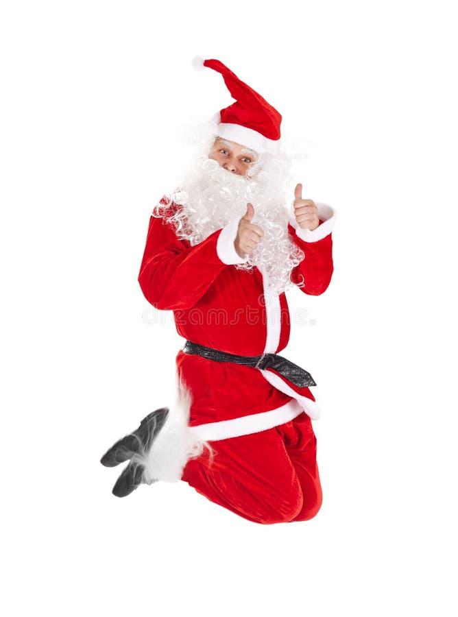 Santa Claus que salta con el pulgar encima de la muestra fotos de archivo