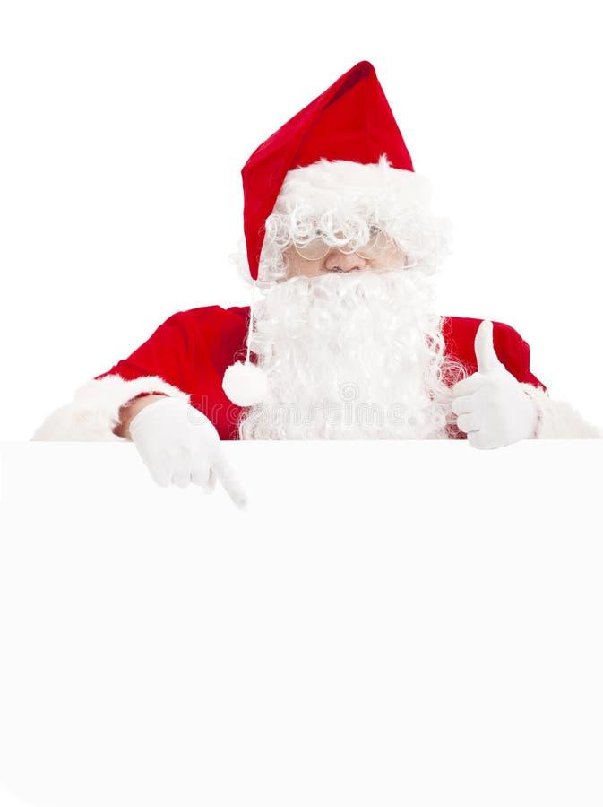 Santa Claus que señala en la bandera en blanco con el pulgar para arriba fotos de archivo