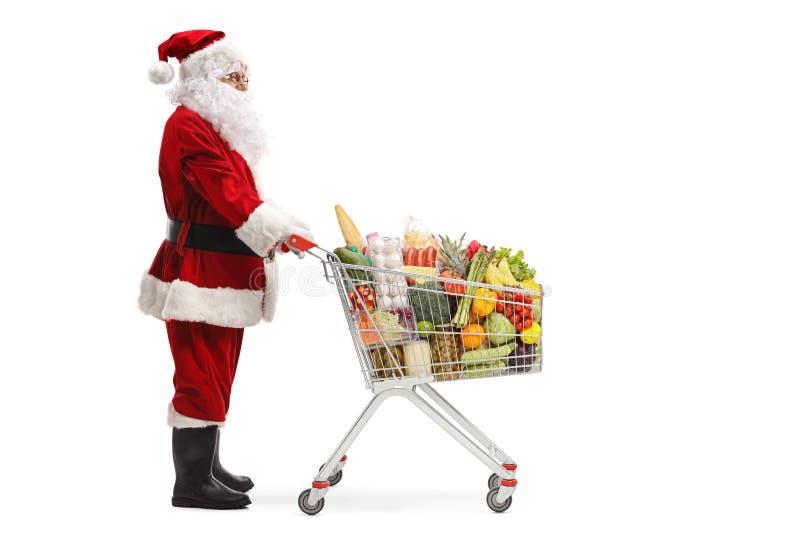 Santa Claus que se coloca con un carro de la compra con la comida imagen de archivo libre de regalías