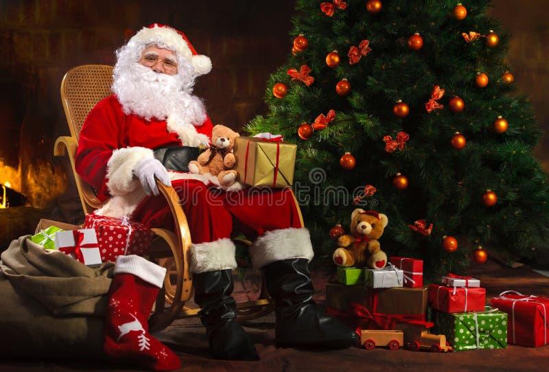 Santa Claus que se sienta delante de la chimenea imagenes de archivo