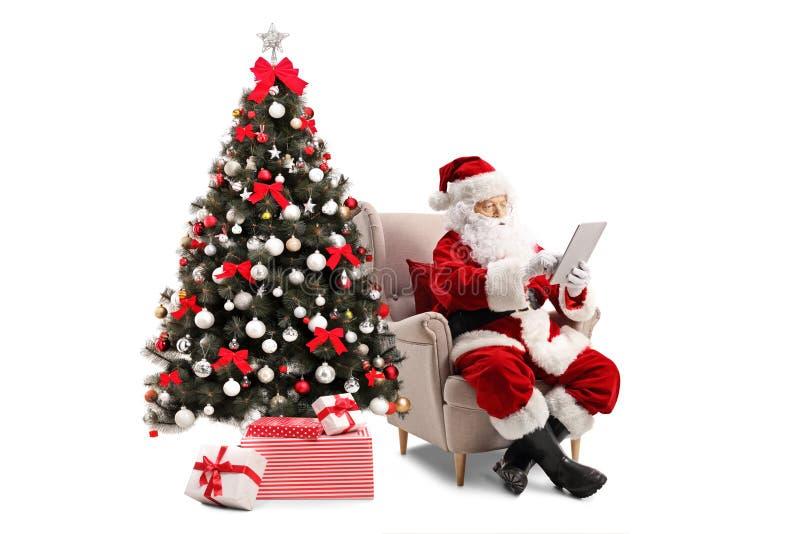 Santa Claus que se sienta en una butaca al lado de un árbol de navidad y fotografía de archivo libre de regalías