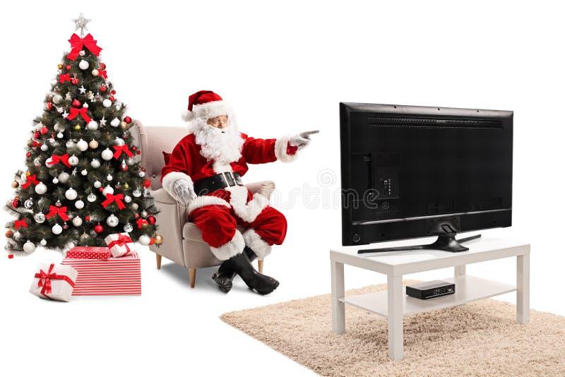 Santa Claus que se sienta en una butaca que ve la TV y que señala a t imágenes de archivo libres de regalías