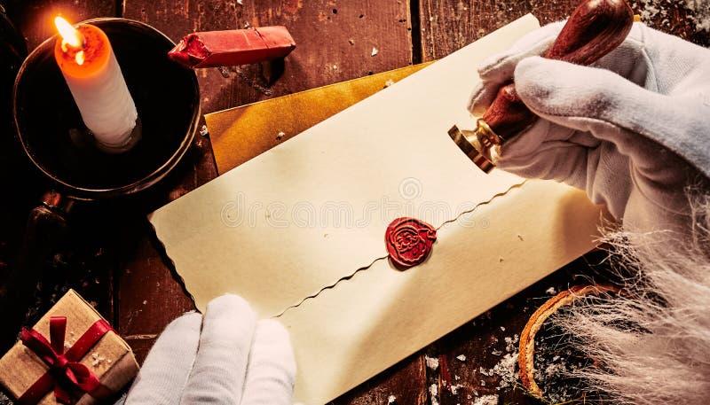 Santa Claus que sela um envelope do vintage com um selo vermelho do Natal da cera que mostra sua cara em um fundo rústico do feri fotos de stock