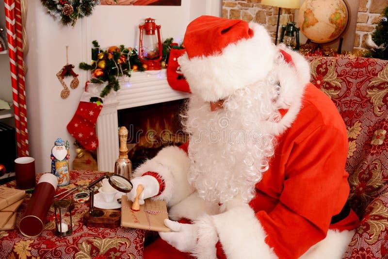 Santa Claus que sela uma letra, olhando através do vidro da lente de aumento imagens de stock royalty free