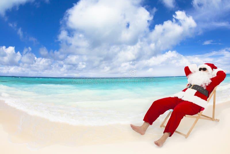 Santa Claus que senta-se em cadeiras de praia Conceito do feriado do Natal fotografia de stock