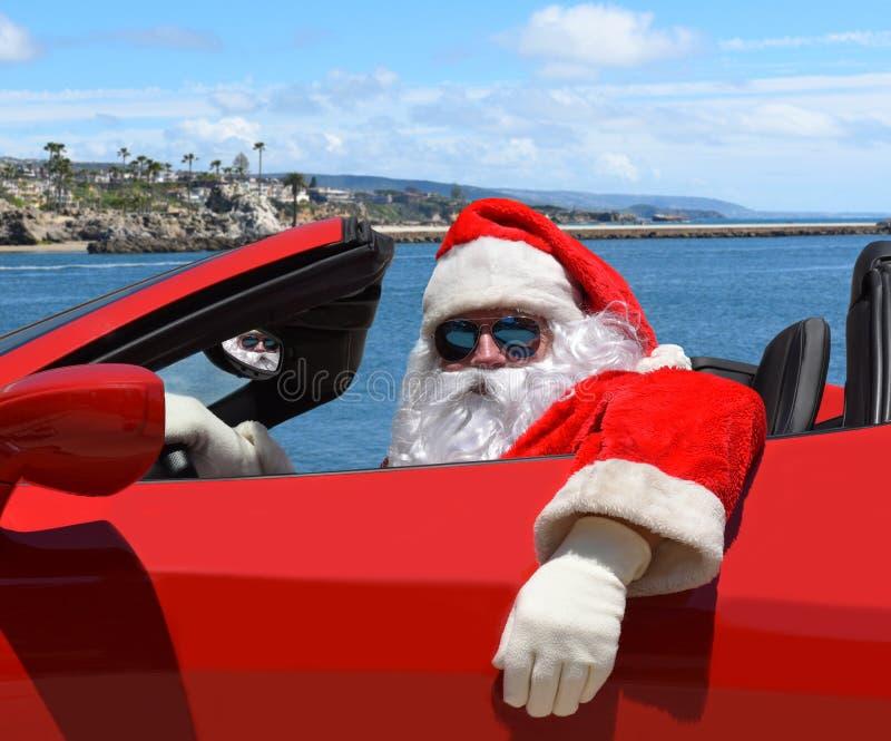 Santa Claus que senta-se em seu carro de esportes do vermelho na praia fotos de stock royalty free