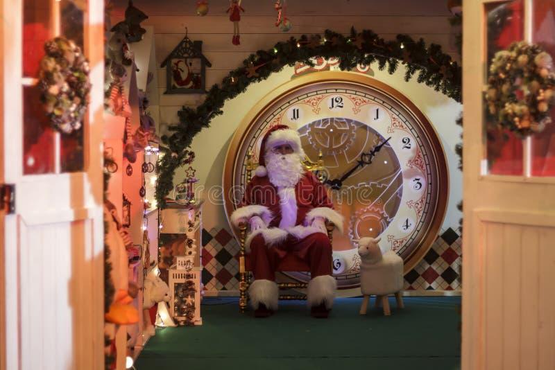 Santa Claus que senta-se em sua poltrona em casa foto de stock