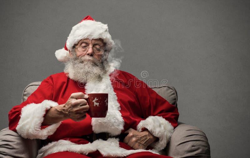 Santa Claus que tiene una bebida caliente fotografía de archivo libre de regalías