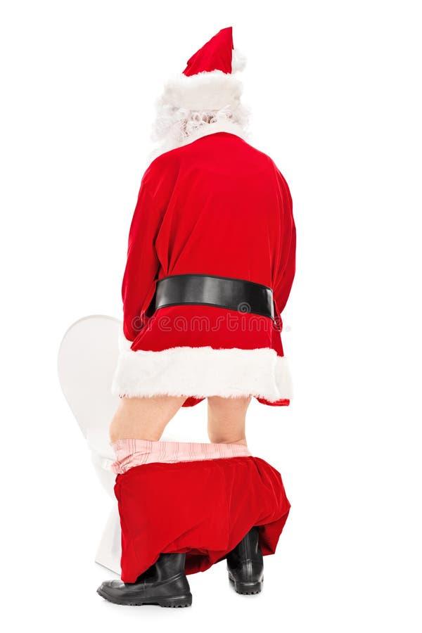 Santa Claus que toma um mijo em um toalete fotos de stock