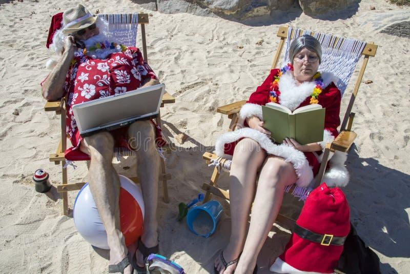 Santa Claus que trabaja en el ordenador portátil y la lectura de señora Claus encendido fotografía de archivo