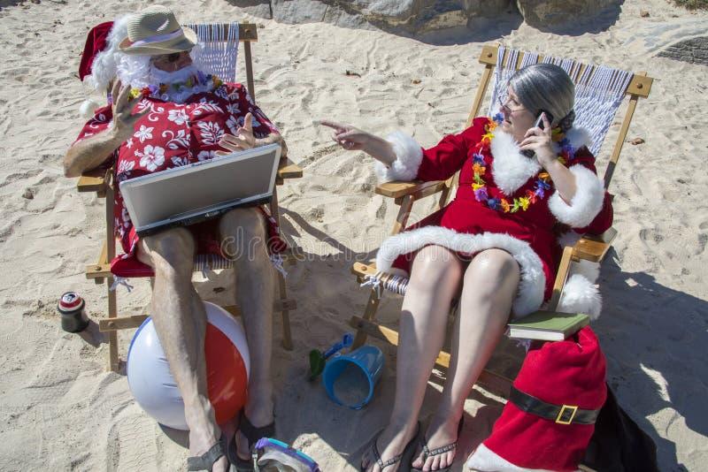 Santa Claus que trabaja en el ordenador portátil y señora Claus en el teléfono encendido fotos de archivo libres de regalías