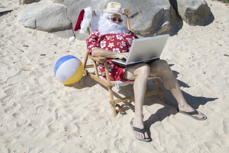 Santa Claus que trabaja en la silla de playa que trabaja con el ordenador portátil imágenes de archivo libres de regalías